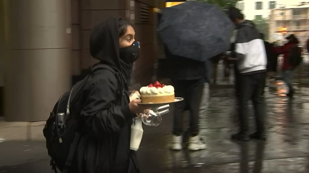 A woman walks with a cheesecake in the midst of riots in downtown Seattle. (Photo via KIRO7.com)